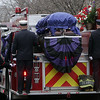 Peabody: Peabody Engine 5 carrying the casket of firefighter Jim Rice slowly rolls down Lowell St. in Peabody on Friday morning. David Le/Salem News