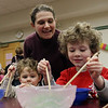 Wendy Glidden, center, of Hamilton helps her sons Seth, 3, left, and Clark, 5, use chopsticks to pick up noodles at the Hamilton-Wenham Library's Lunar New Year Celebration. David Le/Staff Photo