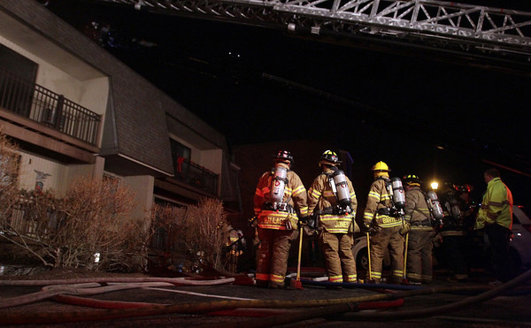 A few Wenham firefighters stand outside a burnt apartment complex on Folley Pond Road in Beverly after the main blaze was extinguished on Wednesday night. David Le/Salem News