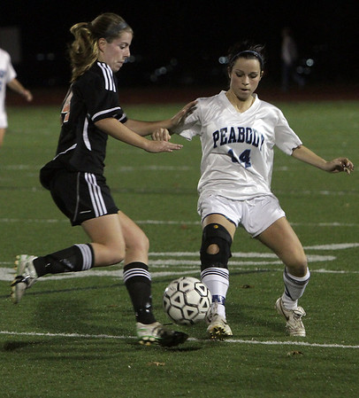 Peabody's Kara Digiacomo (14) right, plays the ball away from an approaching Oliver Ames player on Tuesday night. David Le/Salem News
