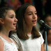 Bentley School chorus members Emily Maggiacomo, left, and Jessica Atwood, right, sing a duet during the spring concert on Tuesday evening. David Le/Staff Photo