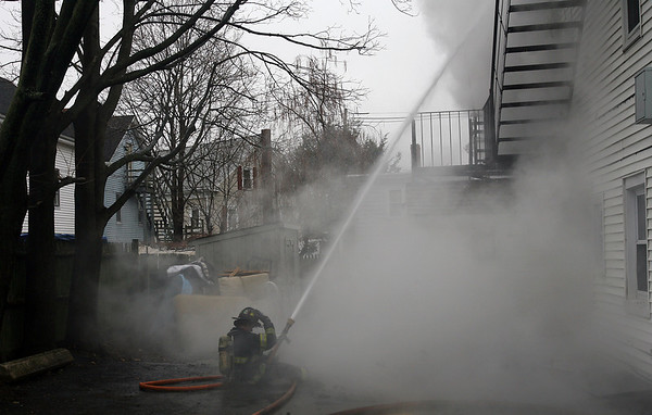 Peabody: A Peabody firefighter sits on the ground in the backyard of 5 Hancock St. and spays water up at the smoking house. David Le/Salem News