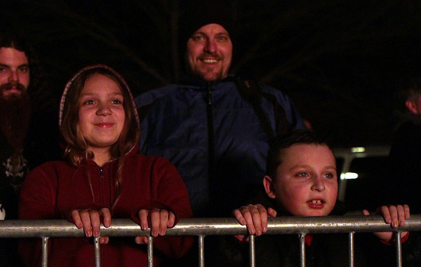 Jasmine Potorski, 10, of Salem, left, Matthew  Milette, and his son Riley, 7, also of Salem, stand along a railing at Dead Horse Beach to watch the annual Christmas Tree Bonfire.David Le/Salem News
