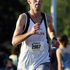 Sean Dunleavy, of Beverly, crosses the finish line of the Beverly 5K Homecoming Road Race on Thursday evening. David Le/Staff Photo