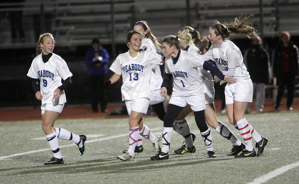 The Peabody High School girls soccer team mobs Katie Brunelle after she scored Peabody's lone goal on the night to give the Tanners a 1-0 victory. David Le/Salem News