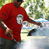 Steve Williams flips over some burgers he is cooking on the grill at the Annual Black Picnic on Saturday afternoon. David Le/Staff Photo