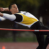Bishop Fenwick senior high jumper Chris Poirier clears the bar in the rain on Thursday afternoon. David Le/Staff Photo
