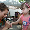 Olimpia Orr, 5, of Beverly, gets a purple butterfly painted on her hand by Annie Wright, also of Beverly, at the first Beverly Farmer's Market of the summer. David Le/Staff Photo