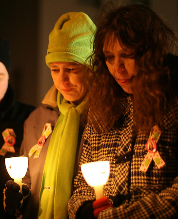 The faces of Kim Flynn, right, mother of Stephanie Moulton, a human service worker who was allegedly murdered last January by a patient, and her sister Tracie Novack, left, are illuminated by candles during a moment of silence at a candlelight vigil on Wednesday night. David Le/Salem News