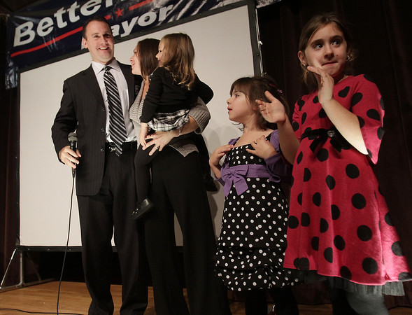 Newly elected Mayor of Peabody Ted Bettencourt, hugs his wife Andrea, holding their daughter Avery, 2, as their other two daughters Allyson, 5, and Taylor, 7, clap for their father and his victory. David Le/Salem News