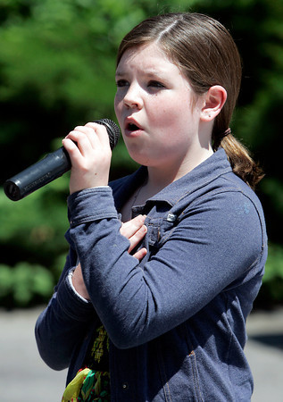 Make-A-Wish child Lindsey Ashworth, 11, of Fairhaven, MA, holds her hand over her heart while she sings the National Anthem prior to the start of the 20th Annual Make-A-Wish Massachusetts and Rhode Island Golf Tournament, held at the Salem Country Club in Peabody on Monday afternoon. David Le/Staff Photo