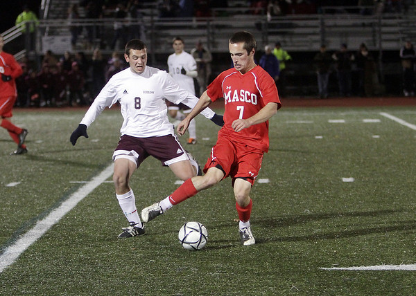 Masco's Charlie Behrens (7) controls the ball while being pressured by Ludlow's Jake DaSilva (8). David Le/Salem News