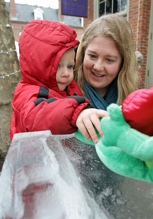 Gus Froeschl, 1, of Salem, reaches for a toy frog sitting on top of a frog ice sculpture outside Maria's Sweet Somethings, with his mother Emily Froeschl, on Essex St. in Salem on Sunday.  David Le/Salem News