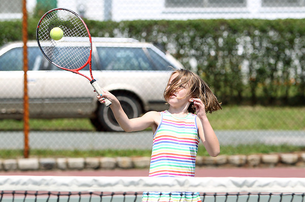 Neave O'Connell, 7, of Beverly, makes contact with the ball, despite having a faceful of hair, while playing tennis on Wednesday afternoon at Kimball-Haskell Park. David Le/Staff Photo