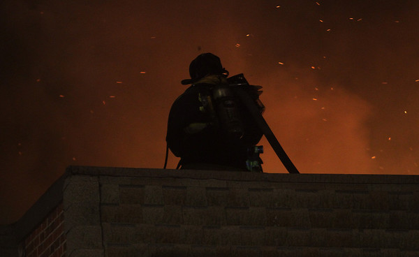 A firefighter tries to combat a massive fire that started in an apartment complex from the rooftop on Wednesday night. David Le/Salem News