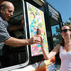 Carlos Rocha, owner of Terry's Ice Cream Shop, hands Paige Kelloway, 17, of Marblehead, an ice cream cone out of his ice cream truck at Devereaux Beach on a hot April afternoon. David Le/Staff Photo