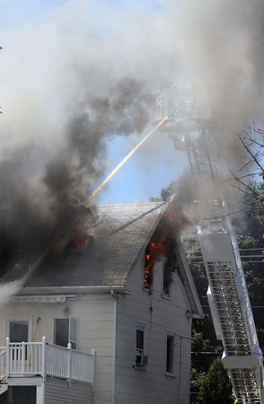 Flames spew out of the topmost windows of 20 Endicott St. as thick smoke engulfs the Peabody firefighters battling the blaze in the basket of the Ladder 1 truck on Wednesday afternoon. David Le/Staff Photo