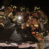 Hamilton: A group of firefighters work together to extinguish part of the roof on a Beech St. home which caught fire on Thursday evening. David Le/Salem News
