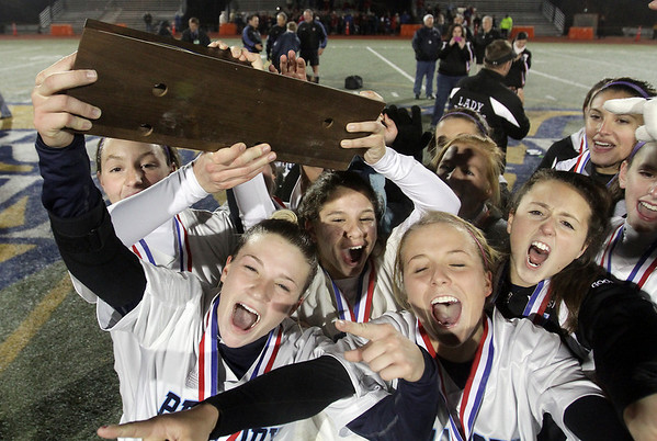 The Peabody High School girls soccer team hoists the D1 Championship Trophy high on Friday night. David Le/Salem News