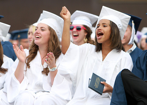 Peabody High School graduates Katelyn Audesse, left, and Luisa Baez, right, cheer on their classmates as they receive their diplomas on Friday evening. David Le/Staff Photo