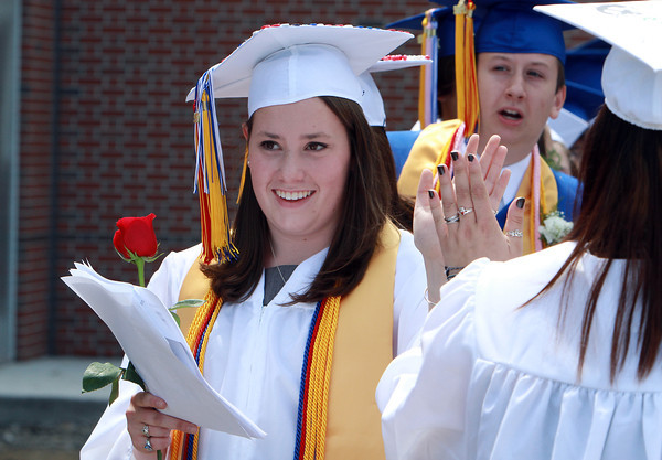 Danvers High School Class President Emily Hodgkins gives high fives to each of her classmates as they line up to march into their graduation ceremony on Saturday afternoon. David Le/Staff Photo