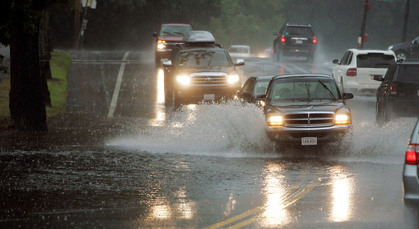 Traffic along Lafayette St. in Salem near the Marblehead line is slowed on Tuesday afternoon during a heavy rain and hail storm as cars try and avoid deep puddles flooding the side of the road. David Le/Staff Photo