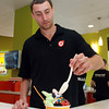 Orange Leaf Manager Steve Giannone pours some toppings on a large cup of frozen yogurt. Orange Leaf is a popular brand new frozen yogurt shop at the corner of Lafayette and Derby Streets in downtown Salem. David Le/Staff Photo
