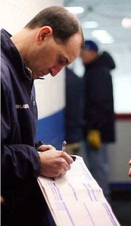 St. John's Prep assistant coach _____________ jots down some last minute notes before gametime. David Le/Staff Photo