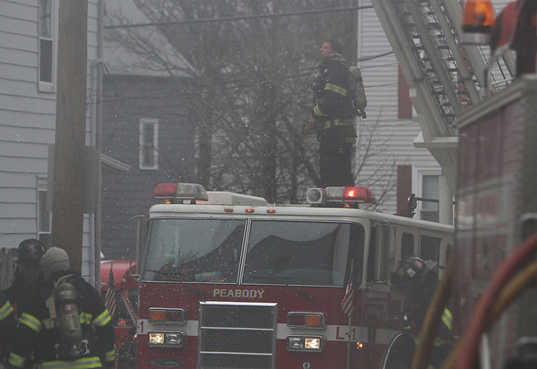 Peabody: A Peabody firefighter stands on top of the ladder truck as he prepares to climb to the top and attack the fire from the roof. David Le/Salem News