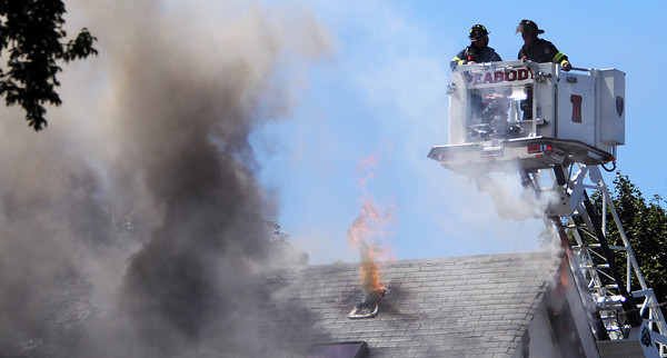 Peabody Ladder 1 firefighters Bob Caruso and Mike Eliuk move out of the way of spewing flames from a hole in the roof of 20 Endicott St. while battling the blaze on Wednesday afternoon. David Le/Staff Photo