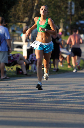 Michelle Brooks, of Beverly, sprints through a few shadows as she finishes the 45th Annual Beverly Homecoming 5K at Lynch Park on Thursday. David Le/Staff Photo