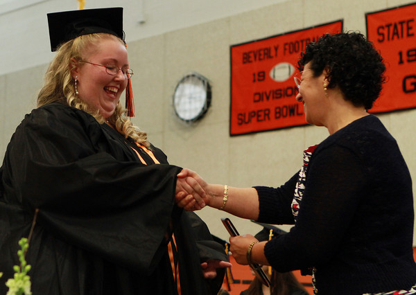 Beverly High School senior Amanda Danskin shakes hands with Maria Decker, President of the Beverly School Committee, as she receives her diploma on Sunday afternoon. David Le/Staff Photo