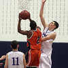 Danvers senior George Merry right, goes up and blocks the shot of Wayland's Jaleel Bell (2) while Danvers junior Eric Martin (11) looks on. David Le/Staff Photo