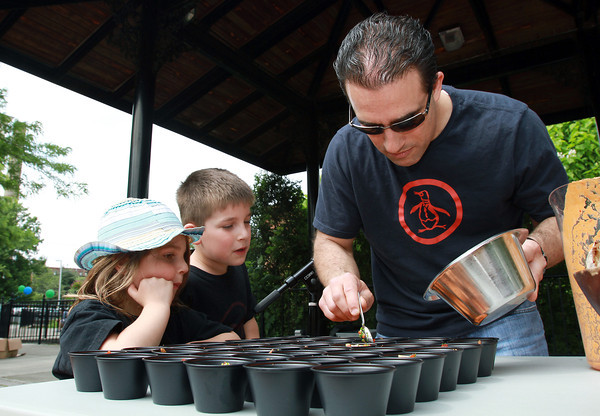 Serena Bettancourt, 4, left, and her brother Marco, 5 1/2, watch as their dad, Tony Bettancourt, owner of 62 Restaurant and Wine Bar in Salem, puts the finishing touches on some gazpacho at the Peabody Farmer's Market on Tuesday afternoon. David Le/Staff Photo