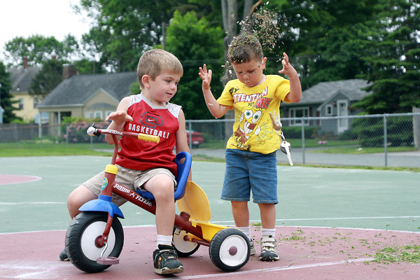 "Roman Sullivan, 5, left, of Beverly, watches as his brother Anthony, 3, showers himself with grass and woodchips they were using as ""bike fuel"" on Tuesday afternoon at Cove Park. David Le/Staff Photo"