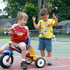 """Roman Sullivan, 5, left, of Beverly, watches as his brother Anthony, 3, showers himself with grass and woodchips they were using as """"bike fuel"""" on Tuesday afternoon at Cove Park. David Le/Staff Photo"""