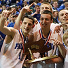 The Danvers Falcons backcourt tandem of junior Eric Martin (11) left, and senior Jon Amico (10) right, hold up the State Championship trophy following a victory over St. Joseph's. David Le/Staff Photo