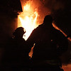 Two firefighters are silhouetted by the massive blaze that caught in an apartment complex on Folley Pond Road on Wednesday night. David Le/Salem News