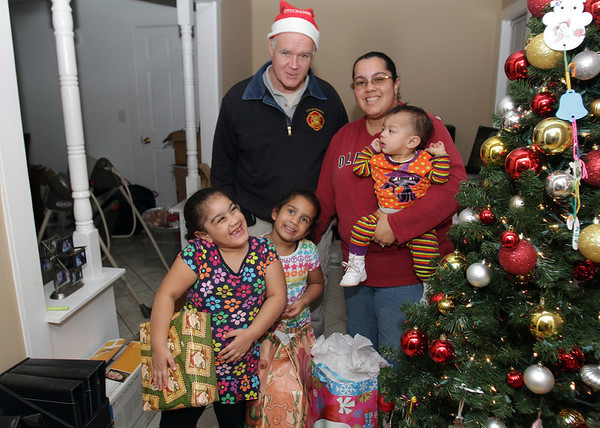 Peabody Veterans Agent Chris Tighe, back left, stands with Madison, 6, Micaela, 5, McKenzie,1, and Melanie Pena after delivering some Christmas gifts on Wednesday afternoon. David Le/Salem News