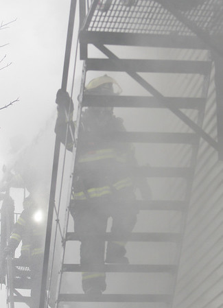 Peabody: Through the thick smoke billowing from 5 Hancock St. a firefighter climbs the stairwell up to the third floor of the burning building.<br />  David Le/Salem News