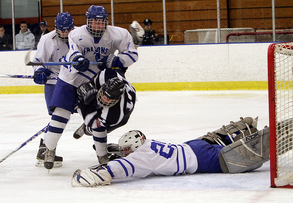 Beverly: Peabody's Eric Costa (14) center, gets checked hard by Danvers' Peter Marshall, left, as Danvers goalie Steve Wilkerson dives to make a save. David Le/Salem News
