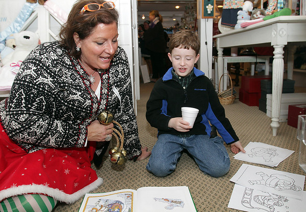 Snowflake the Elf from Elf Works reads Christmas stories with Michael Cunniff, 8, of Marblehead on Sunday afternoon.David Le/Salem News