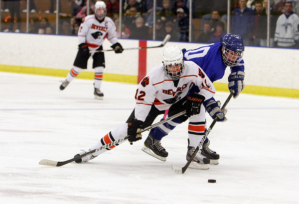 Salem: Beverly's Jack Morency (12) left, tries to ride Danvers captain Joe Strangie (10) off the puck on Friday night., David Le/Salem News