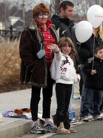 Annie Hudson, 5, of Beverly, and her mother Sarah, wave to paraders along Elliot St. in Beverly on Sunday. David Le/Salem News