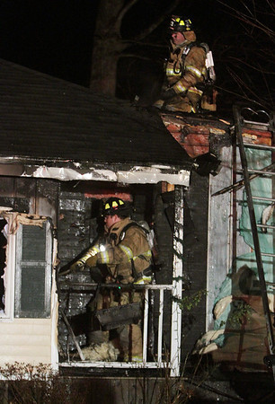 Hamilton: A firefighter sits on top of the roof of a Beech St. home, as another responder breaks down some of the outside panels of the badly burned home on Thursday evening. David Le/Salem News