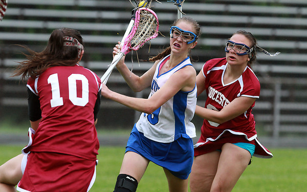 Danvers freshman Meaghan McKenna, center, manages to get away a shot while being pursued by Gloucester's Kenna O'Maley, left, and Sara Sidlowski, right, on Tuesday afternoon. David Le/Staff Photo