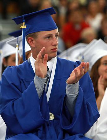 Swampscott High School senior AJ Baker applauds Class President Kristin Wheeler following her speech on Sunday afternoon. David Le/Staff Photo