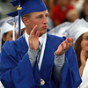 Swampscott High School senior AJ Baker applauds Class President Kristin Wheeler following her speech on Sunday afternoon. David Le/Staff Photo