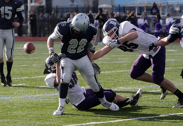 Hamilton-Wenham running back Elliott Burr (22) fumbles the football after being hit by two Bourne defenders. David Le/Salem News