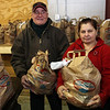 Volunteers at St. Joseph's Food Pantry Nelson Sanchez and Maria Lacerta, both of Salem, hold bags of food they give out to Salem residents. David Le/Salem News